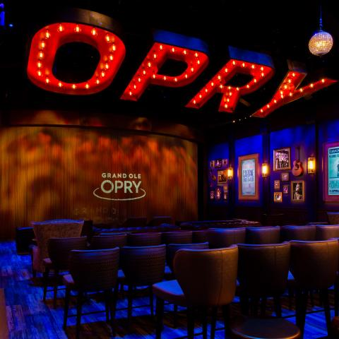 "The new Circle Room at the Grand Ole Opry featuring a large ""Opry"" sign suspended from the ceiling, a stage, theater seating, memorabilia from stars and more."